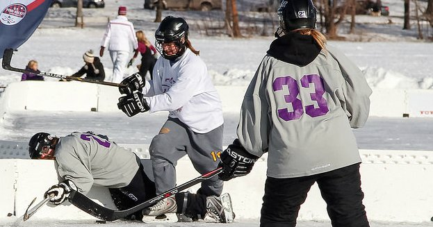 Image of female hockey player body checking opponent.
