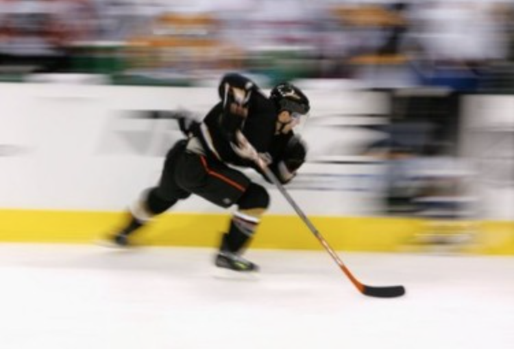Image of hockey player skating fast.